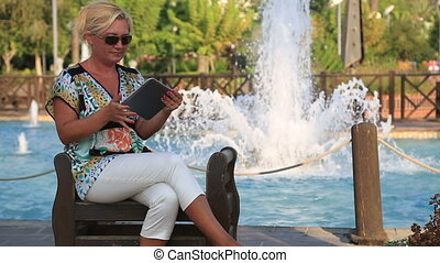 woman using digital tablet near the park fountain