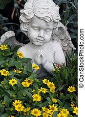 little praying angelic figure among the growing flowers on tomb,