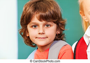 Portrait of cute schoolboy looking straight with big...