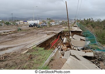 Destroyed road by hurricane Odile and a track full of dirt
