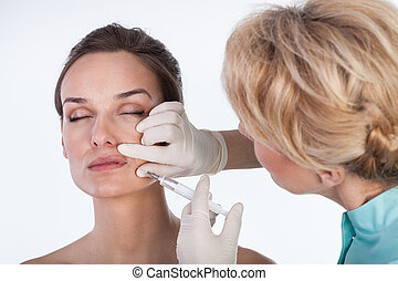 Doctor making a mouth botox in beauty clinic