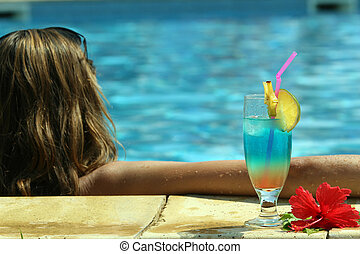 girl in pool with cocktail - fresh cocktail standing by the...