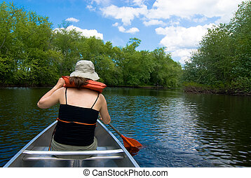 Idyllic canoeing on a gentle river - Young woman canoeing on...
