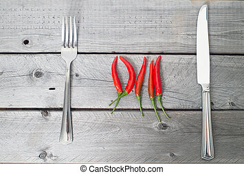 Spicy meal concept with chilis, knife and fork over a wooden...