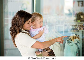 Mother with baby at shop window