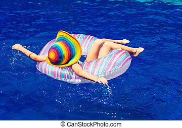little girl lying on the inflatable rubber circle in the...