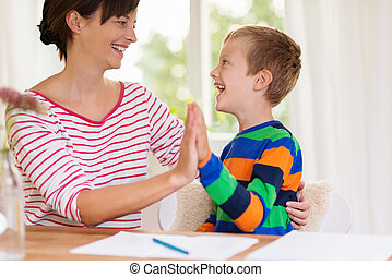 Young boy laughing with his mother or teacher and clapping...