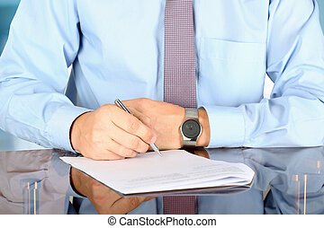 Businessman sitting at office desk and signing a contract by...