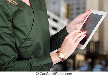 Busineswoman holding and working with a digital tablet...