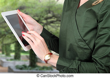 Busineswoman holding and working with a digital tablet Trees...