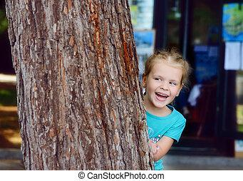 peek-a-boo - lovely little girl hiding behind the tree