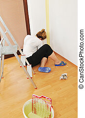 Young woman painting wall with paint roller