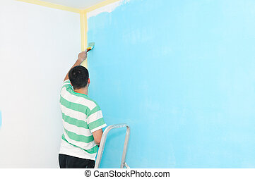 Young adult male painting wall - Home improvement: Young man...