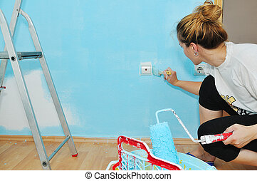 Young adult couple painting wall - Home improvement: Young...