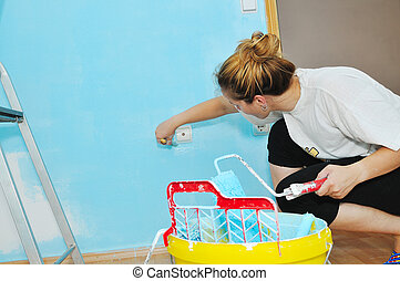 Young Young woman painting wall with paint rollercouple...