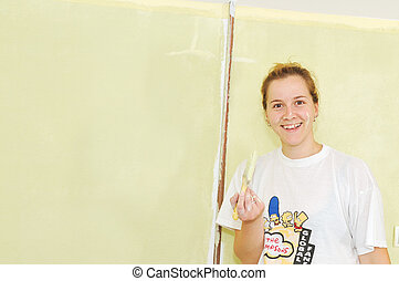 Home improvement: Young woman painting wall with paint roller