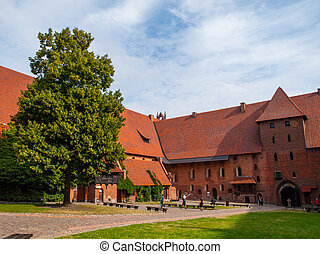 Malbork courtyard with big tree and green lawn, Poland