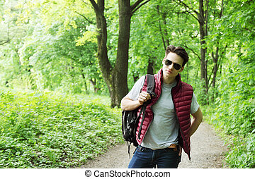 man walks in the forest - young man with a backpack walks in...