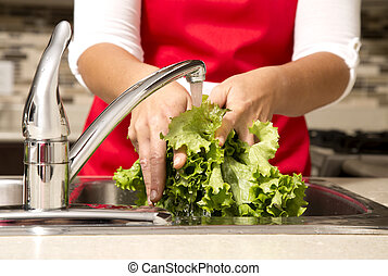 washing vegetables - woman washing vegetables in the sink...