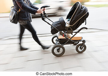Woman with pram - Woman in blurred motion with baby in pram