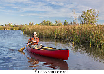 afternoon canoe paddling - senior male paddler paddling a...