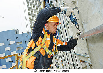 builder at facade construction work - worker builder making...