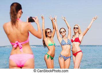 group of smiling women photographing on beach - summer...