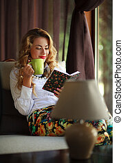 Happy young woman reading book - Happy young woman drinking...