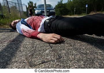 Bleeding man lying on the street after car accident