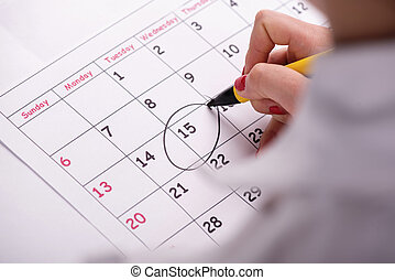 Close-up photo of calendar with a datum circled - Close-up...
