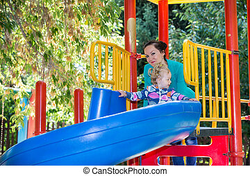 Happy adorable girl with mom on childrens slide on...