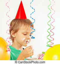 Young child in festive hat eating piece of birthday cake