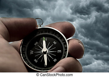Hand holding black compass on thunder sky background