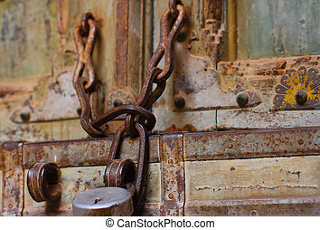 Padlock on a chain old and discoloured