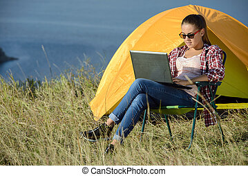 Camping - Portrait of succesful woman with laptop sitting in...