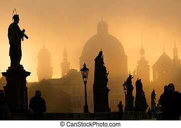 Silhouette of statue and tourists on Charles bridge during...
