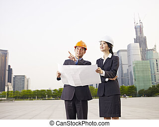 asian business people with safety hats and blueprint.