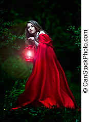 beautiful woman with red cloak and lantern in the woods by...