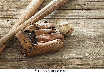 Old baseball, mitt and bats on wood - An old baseball, mitt...