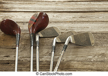 Old golf clubs on rough wood surface - Old golf clubs on...