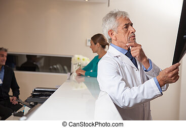 Mature male doctor analyzing x-ray test, doctor and assistant in