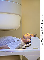 Laying man undergoing medical scan.