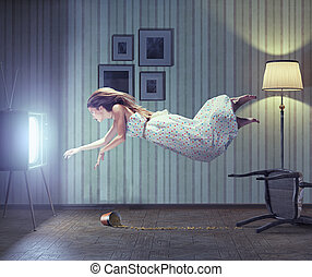 woman and tv - Young beautiful woman flying to tv screen in...