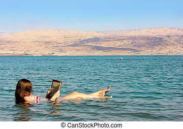 young woman reads a book floating in the Dead Sea in Israel...