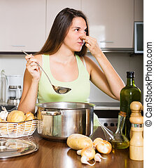 woman takes lid off pan and feel musty smell - Young woman...
