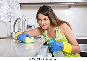 Woman cleaning kitchen - Happy young housewife in apron...