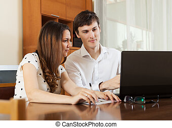 Young couple looking financial documents in laptop at table...