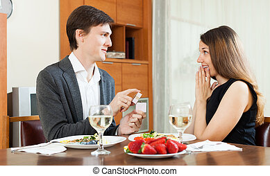 Man presents girl ring - Man presenting to amazed girl ring...