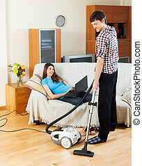 Man cleaning while woman lying with notebook - Man cleaning...