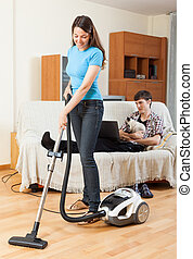 Wife cleaning and husband rests - Wife cleaning with...